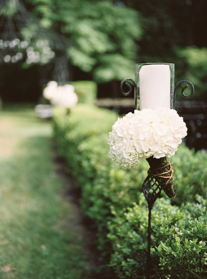 The ceremony decor went beyond the aisle itself, with wrought iron pedestals lining the perimeter of Lord Thompson Manor's quaint gardens, boasting bouquets of fresh white hydrangeas and pillar candles. The additional arrangements added to the ceremony's romantic, elegant aesthetic without feeling over-the-top.