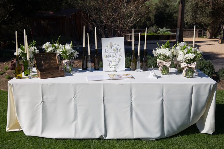 "The traditional guest book was displayed on a white tablecloth-covered table, with a sign that read ""I have found the one whom my soul loves."" Long white candlesticks and lush flower arrangements decorated the rest of the table."