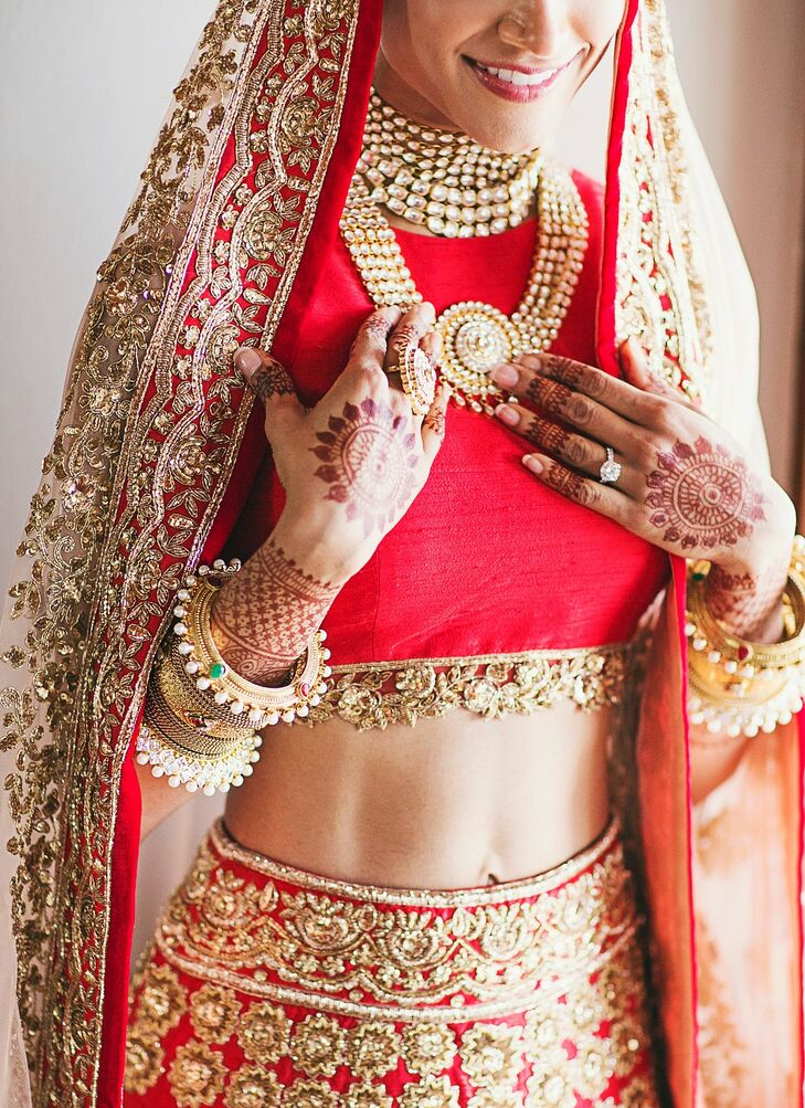 "Melanie accented the intricate embroidery of her Manish Malhorta bridal lehenga with traditional gold necklaces and stacks of bangles on each arm. Her most memorable moment came when her father arrived to walk her down the aisle, seeing Melanie in her wedding dress for the first time: ""I took one look into his proud, loving eyes and couldn't hold back my tears of love and joy,"" Melanie says."