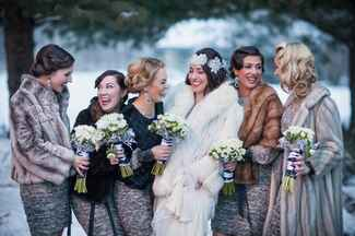 Bride and her bridesmaids laughing in fur wraps outside
