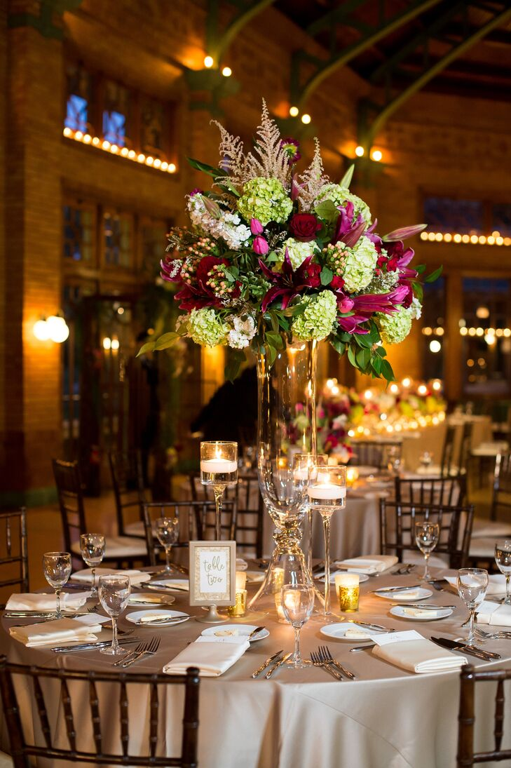 Eye-catching flower arrangements comprising lush greenery, moody red roses and pops of pink filled the elegant reception space at Cafe Brauer in Chicago, Illinois.