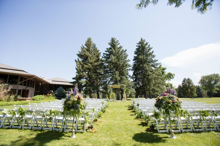 "While the couple originally planned to host the wedding in their backyard, the stress of an at-home event eventually lead them to The Boulder Country Club in Boulder, Col. While the pair opted for an indoor reception, they hosted their ""I do's"" outdoors on the expansive lawn overlooking acres of lush trees and the mountains beyond. To provide a taste of the whimsical decor to come, the pair lined the aisle with ferns, florals and moss and placed a traditional chuppah dripping in ferns, full bright blooms and succulent and moss-filled glass orbs at the end of the aisle, under which laid a silk carpet the pair had purchased in Turkey. ""After my dad walked me down the aisle, Nick bent down and unstrapped my shoes, and we both stepped onto the carpet barefoot,"" says Kat. ""We stood there holding hands, surrounded by some really special gemstones that we had collected over the years. Standing under the gorgeous wedding arch, with beautiful flowers and air plants hanging around us, everyone else just seemed to disappear. It was a truly intimate and special way to create a space for just the two of us."""