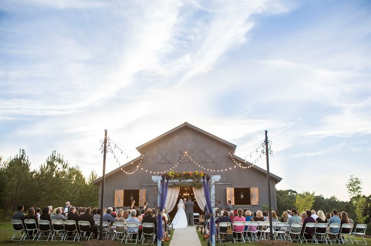 Candice and Nathan wanted a barn backdrop for their outdoor wedding and an on-site indoor reception venue. They found just that at the Cotton Market Venue in Pearl, Mississippi. Their ceremony highlighted the space, with pumpkin aisle decor, navy tulle along the wedding arch and neutral curtains by the barn entrance.