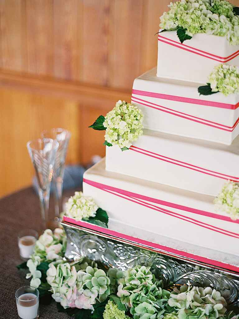 Four-tiered, white wedding cake with pink pattern