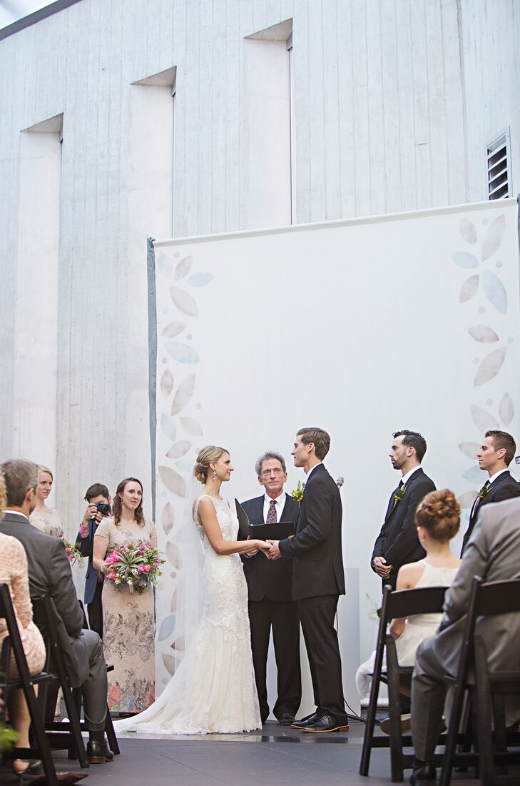 The main ceremony decor was a large backdrop for the altar—an expansive piece of white fabric with metallic floral prints on the edges and proteas and other desert flowers along the aisle.