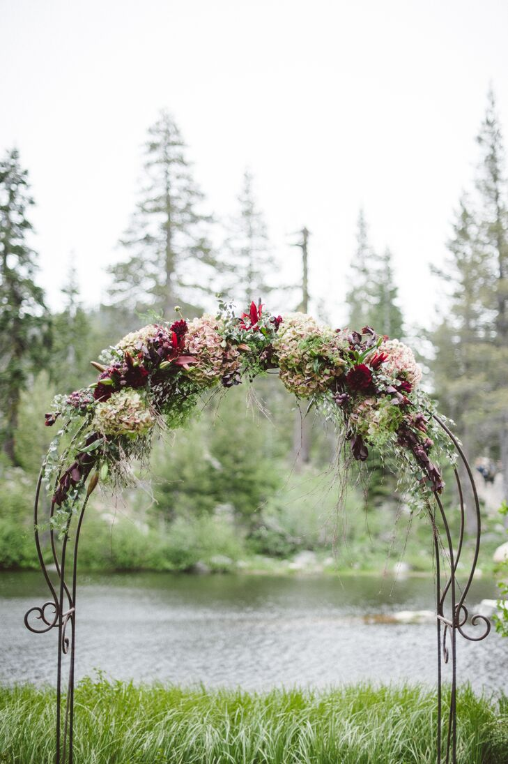 Kimberly and Derek had their wedding ceremony outside near the lakefront in Alpine Meadows, California. They said their vows at the wrought- iron wedding arch, which was accented in a variety of hydrangeas mixed with greenery.