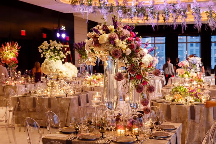 "Using a vibrant color palette and fresh, seasonal blooms from a local flower market, David Beahm created a series of one-of-a-kind centerpieces for Allison and Jason's reception tables. ""Each centerpiece was different, which made each table look like a work of art,"" says Allison. ""In addition, we hung whole Vanda orchids above the dance floor, which was inspired by the George V Hotel."""