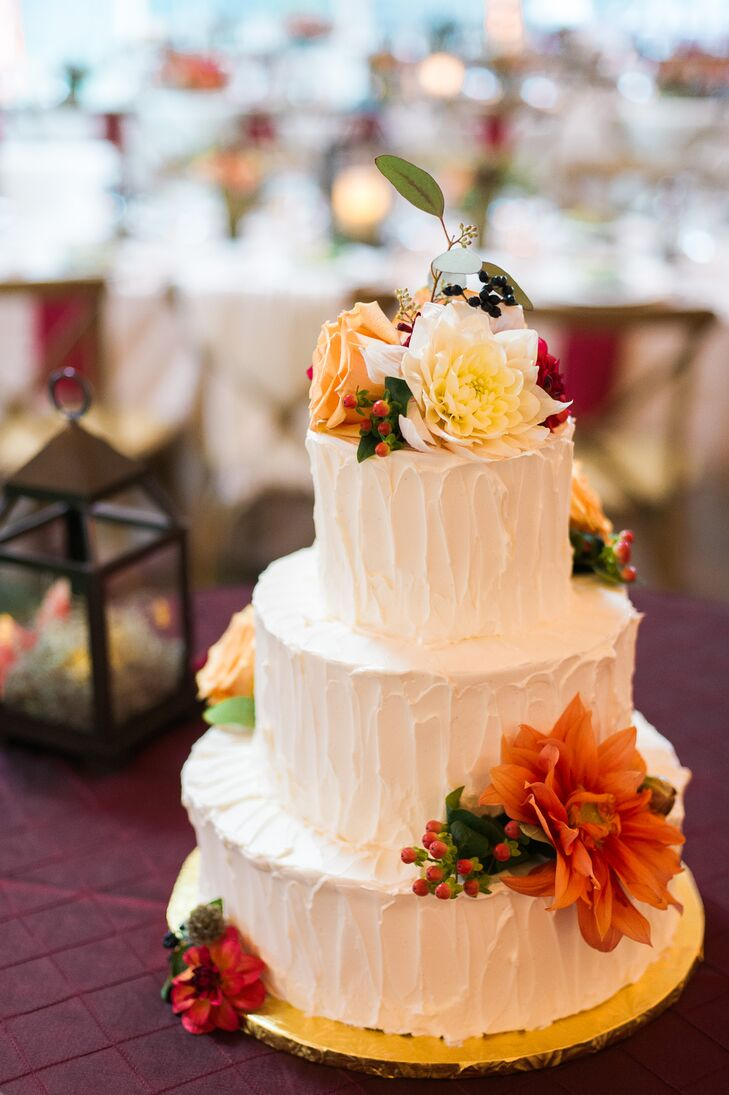 The three-tier buttercream-iced cake was decorated with fresh blooms on the top and sides. The flavors consisted of carrot, pumpkin spice and almond with cream cheese, to go with the fall season.