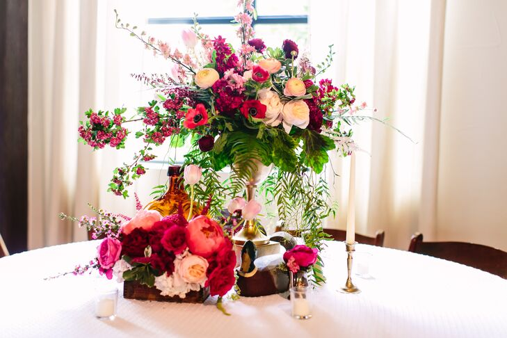 Round guest tables had textured white linens topped with overflowing flower boxes and tall vases filled with whimsical blooms. The bold and bright arrangements included garden roses, anemones, ranunculus, peonies and astilbes. Eclectic vintage decor and a host of candles surrounded the floral centerpieces.