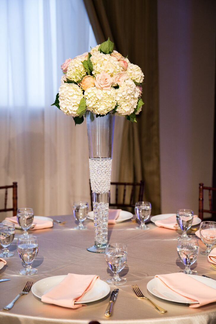 Inside the ballroom reception, round dining tables dressed in champagne-colored tablecloths were set with white plates and pink napkins. A tall glass vase filled with a round assortment of ivory hydrangeas and pink roses decorated the middle of the dining table.