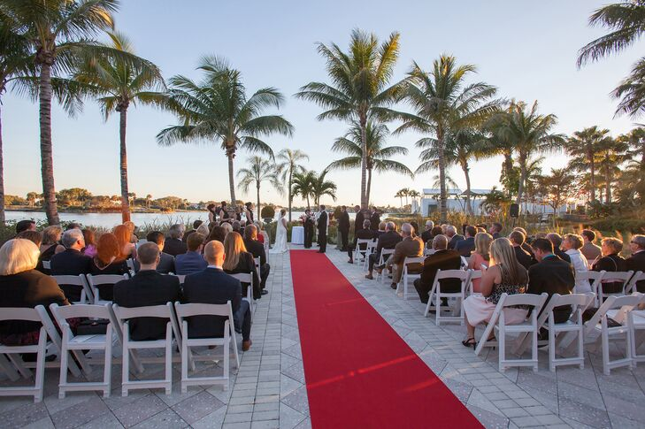 To avoid overshadowing the palm-tree-lined setting, Courtney and Aaron accented their ceremony with a simple red runner and white folding chairs.