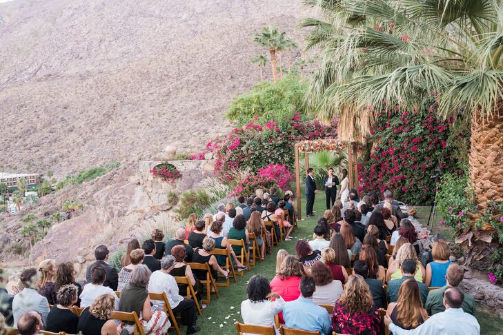 """The ceremony site offers a beautiful view of the mountains and is a gorgeous natural setting,"" Anne says. The couple said vows under a fruitwood chuppah with succulents, orange and coral roses."