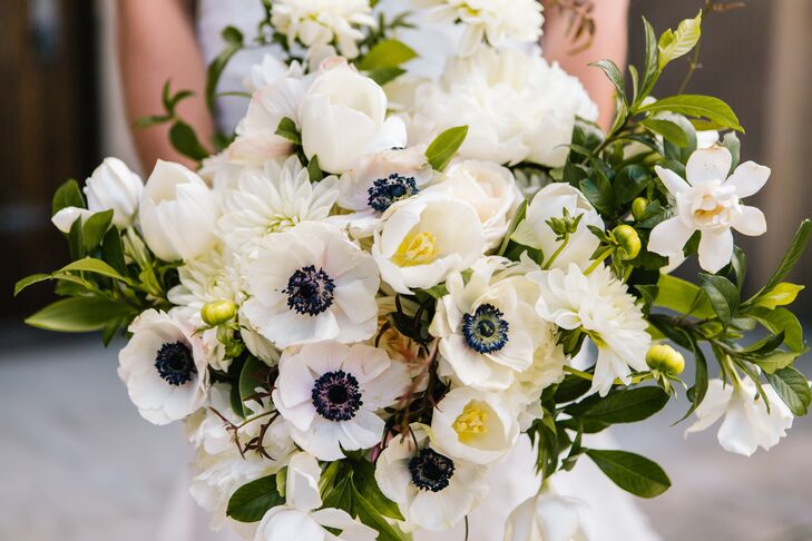 The bride's bouquet carried the theme of white, gray and green with notes of lavender. Included were peonies, garden roses, tulips, ranunculus, anemones and white lilacs. The bridesmaids had similar versions of the bouquet.