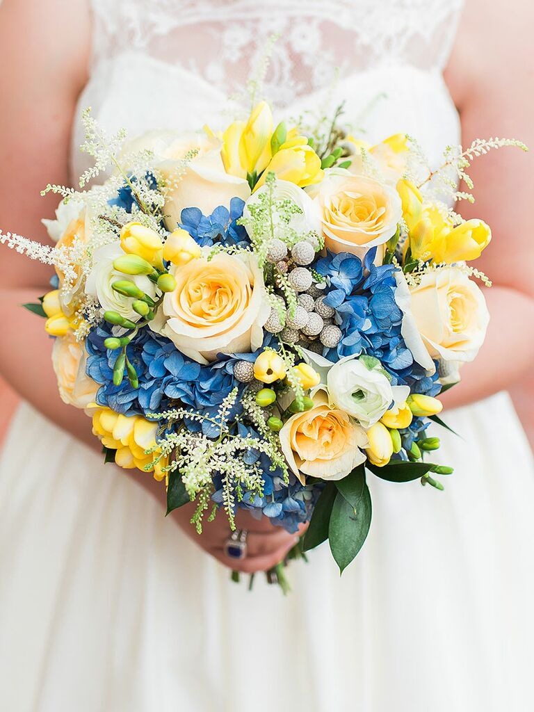 The best blue wedding flowers and 16 gorgeous blue bouquets blue and yellow wedding bouquet with ranunculus roses hydrangea brunia berries and astilbes junglespirit Images
