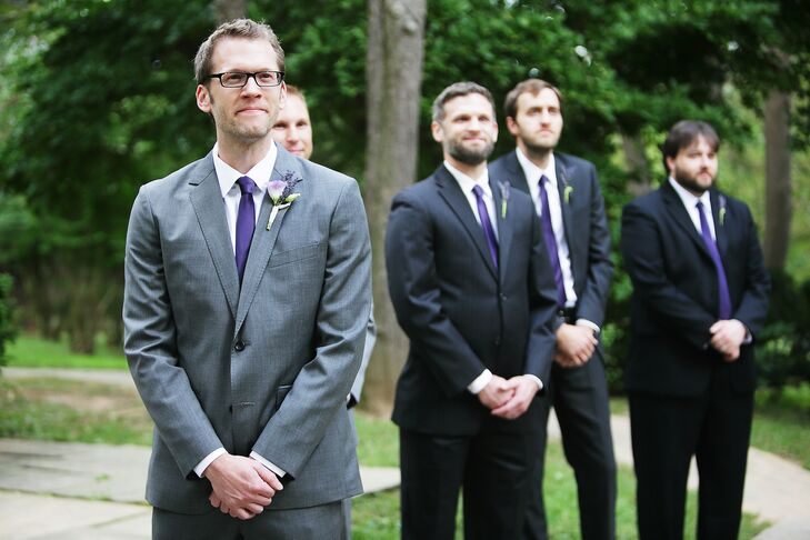 Todd wore a gray Bonobos suit on his wedding day. He also wore a purple tie and lavender boutonniere. His groomsmen wore black suits with purple ties.