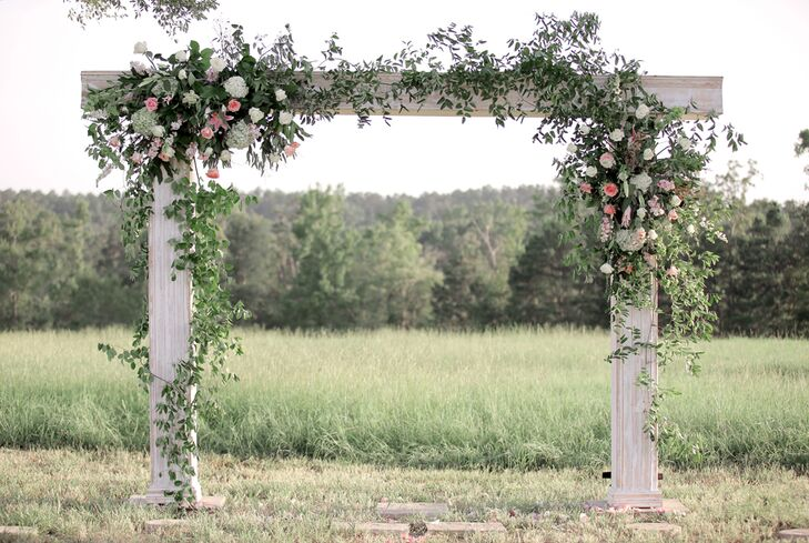 White Wooden Wedding Arch With Greenery And Flowers