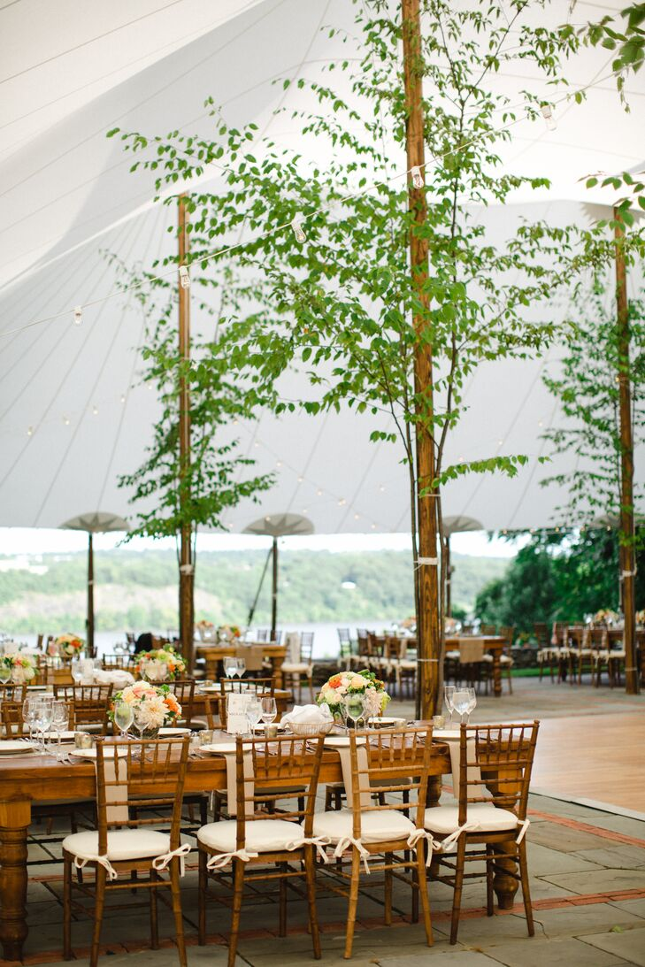 """When I looked at photographs of other weddings in the Hudson Valley, I repeatedly found myself drawn to the work of Linda Baldwin. She creates beautiful arrangements that are elegant and natural,"" Hannah says. For the reception, she infused the expansive tent with woodland whimsy by adorning the tent poles with tree saplings."
