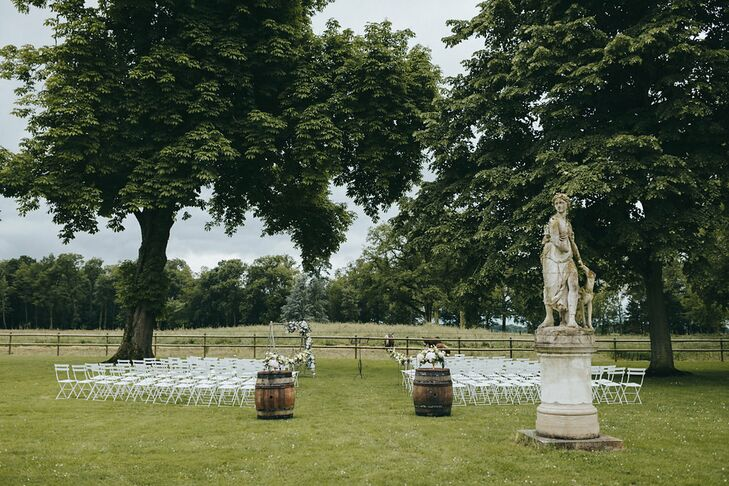 The ceremony took place between two trees on Chateau de Varennes' lush lawn. Two wooden barrels topped with flower arrangements sat at the entrance to the aisle.