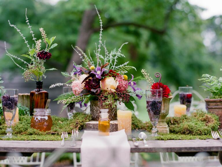 Outdoor wedding reception with moss table runner
