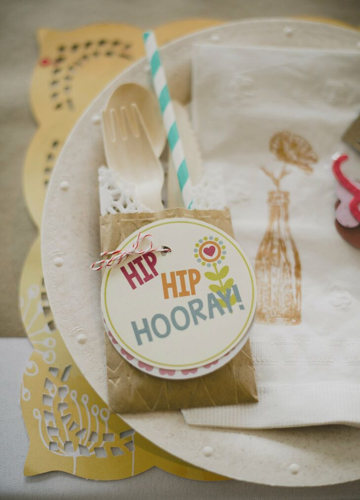 A tag with Hip Hip Hooray! written on it was attached to the silverware. Everything for our wedding was DIY, from the kraft paper stationer that I designed to the pastel ribbon wall, as well as the hand-stamped napkins for our relaxed place settings, says Kristy.