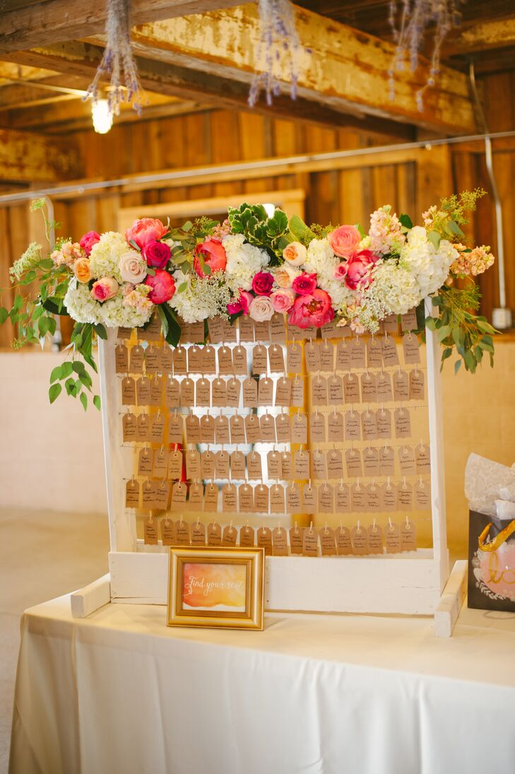 Brian built a white frame for guests to find their kraft paper escort cards, dangling on pieces of string. A pink and white lush flower arrangement filled with peonies, hydrangeas, ranunculus and more decorated the top, incorporating the garden vibe into the display's overall look.