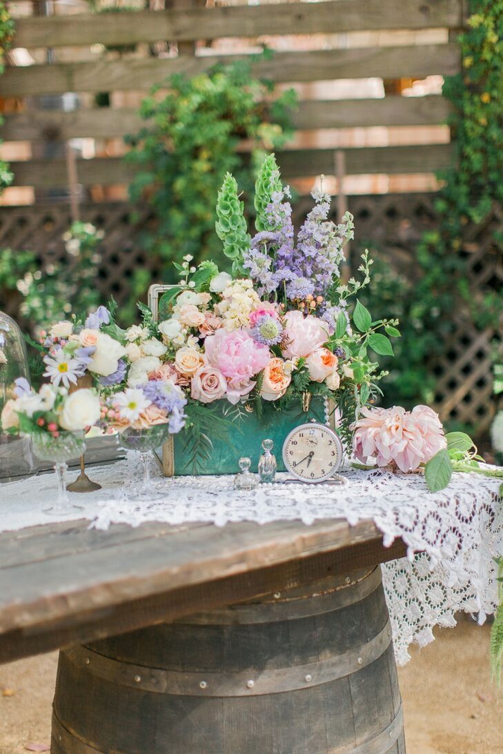 The centerpieces weren't the only place where Lotus and Lily's creativity shined. Lavish arrangements of pastel garden roses, Bells of Ireland, hyacinths, dahlias and more in flirty, feminine shades of pink and purple were woven throughout the reception, infusing the natural setting with color and vibrancy.