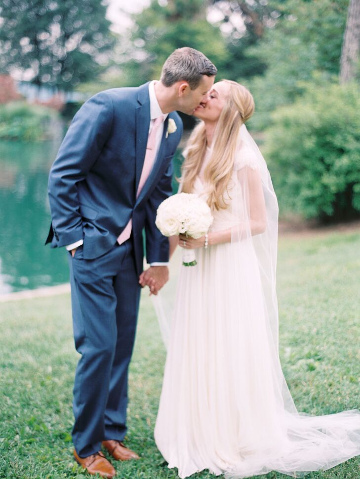 Kristen and Andrew kissed as they held hands with a natural backdrop behind them. The bride held an ivory bouquet with an assortment of roses, hydrangeas, peonies and dusty millers.