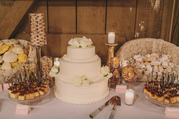 The couple opted for a traditional, three-tiered, white, round wedding cake and topped it with fresh white roses.