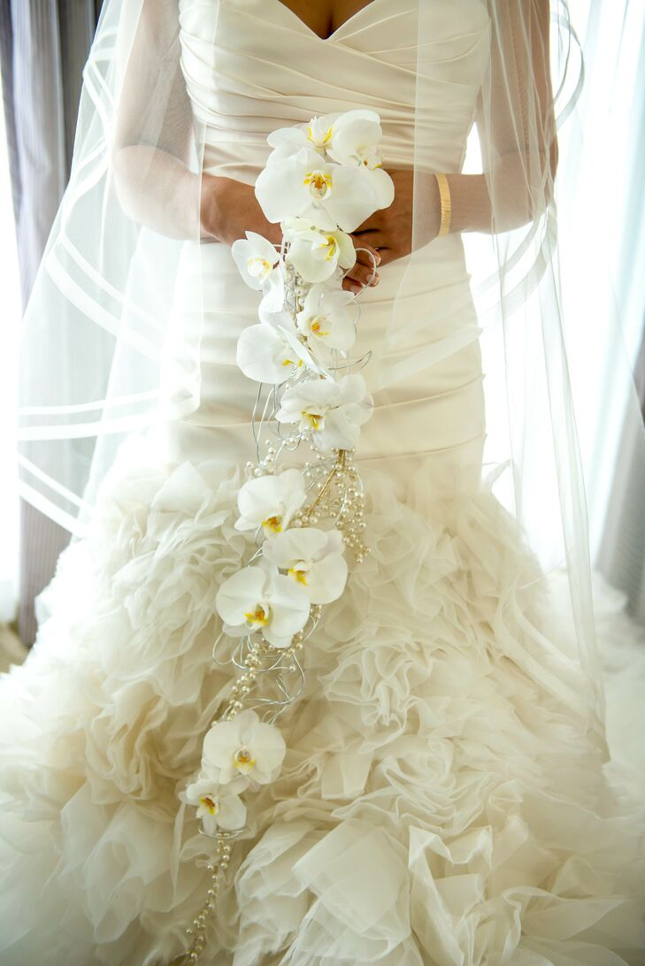 Instead of a traditional bridal bouquet, Jacqueline carried a beautiful cuff of cascading white orchids and pearls matching the wedding's elegant style.