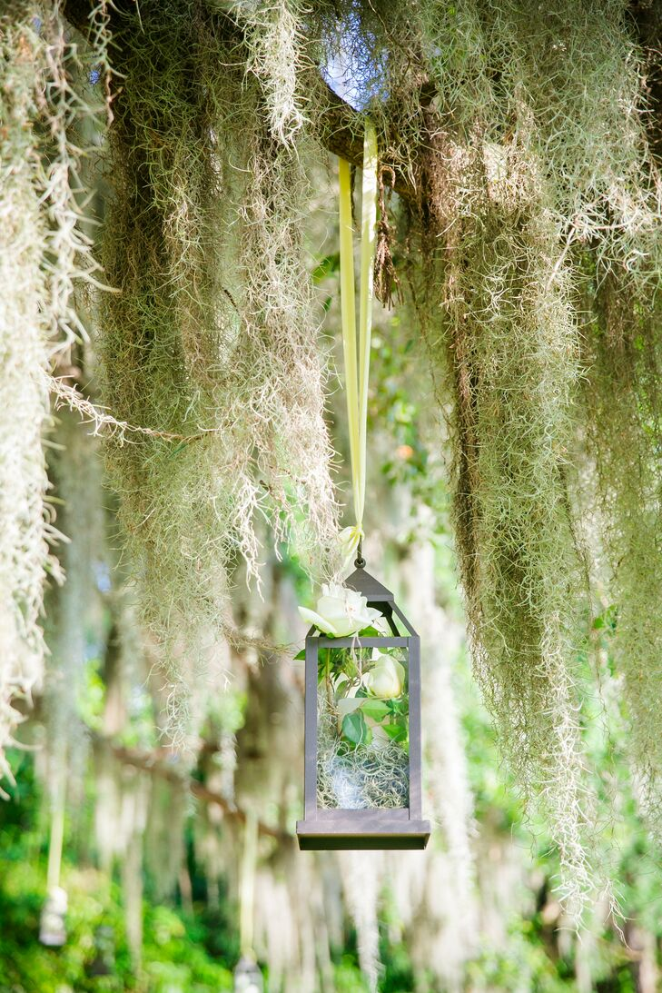 Metal lanterns filled with florals hung from the Spanish-moss-covered oak trees, adding a romantic and rustic atmosphere to Carly and Spencer's ceremony.
