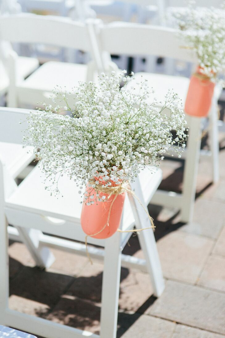 The outdoor ceremony took place at Aspen Lakes Golf Course in Sisters, Oregon, where white folding chairs faced the altar. Hanging bottles painted coral filled with baby's breath lined the aisle.
