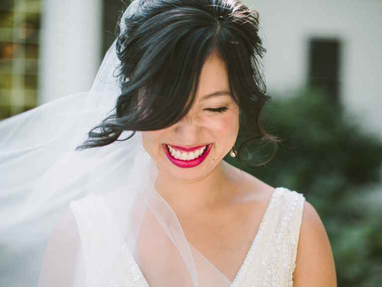 A bride with bright pink lips laughing