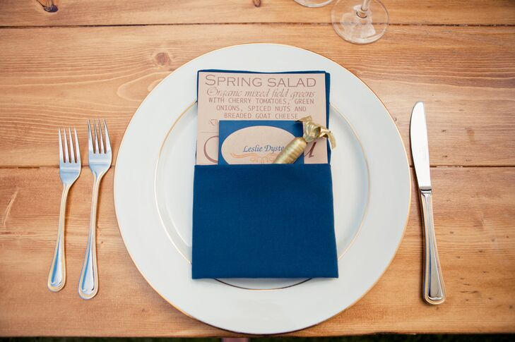 White and blue seating cards were placed at each dinnerware set, which was paired with the menu for the evening. Both pieces of stationery were placed inside a folded navy blue napkin, with a gold carrot decoration sticking out. Sand dollars and pigs were seen at other settings, showing what each guest had ordered on the menu.