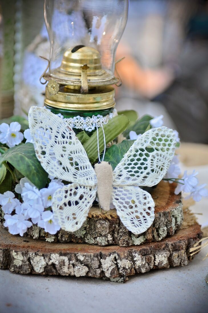 Their garden setting at Gigi's Country Garden in Plant City, Florida, wasn't lost in the decor. The centerpieces had tiered, natural wood slabs below actual oil lamps. Fabric flowers and greenery circled the bases. To tie in both their setting and country design, Heather and Jeremy topped the accent with a burlap and lace butterfly.