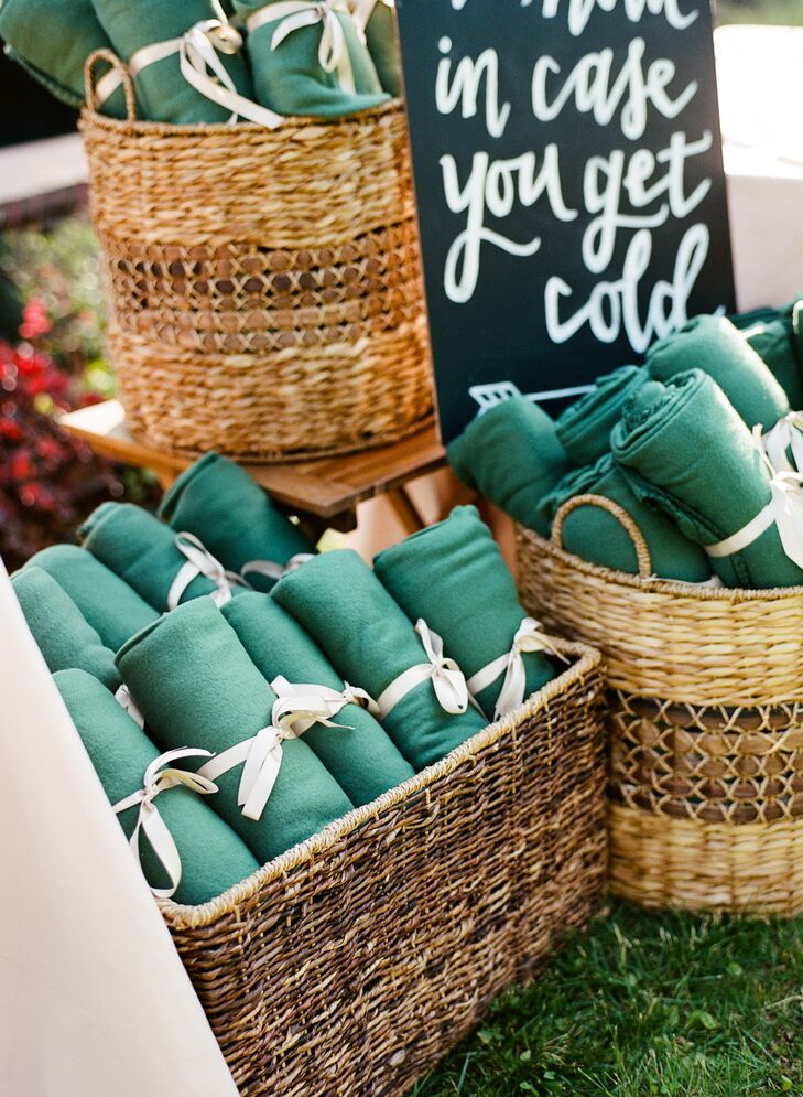"Jamie and Alex wanted guests to stay warm during their ocean-side celebration, so they provided blankets wrapped with satin ribbon. They were displayed in baskets with a cheeky hand-painted sign that read ""To have and to hold, in case you get cold."""