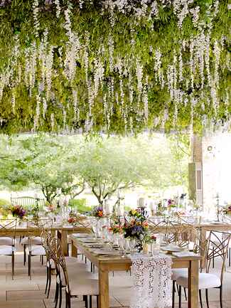 Outdoor tented wedding decor with hanging flowers