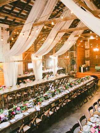 Rustic barn wedding reception space with draped white fabric decor