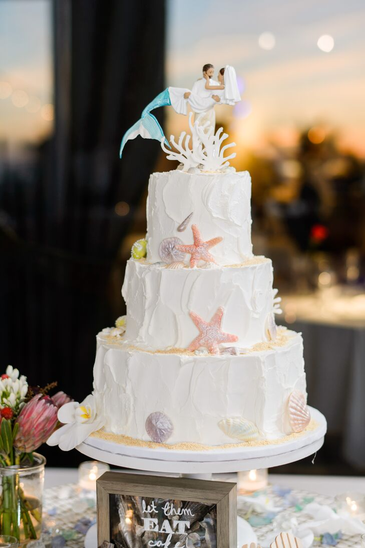 """It may have looked simple on the outside, with spackled buttercream and sugar seashells, but inside were two amazing flavors—marbled chocolate sea salt caramel and classic white with guava for a fresh option,"" Nicole says. The pair completed the sea-inspired cake with a custom mermaid cake topper for a punch of extra panache."