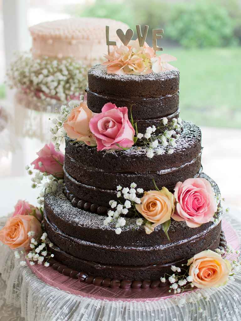 Three-tiered chocolate wedding cake with powdered sugar and roses