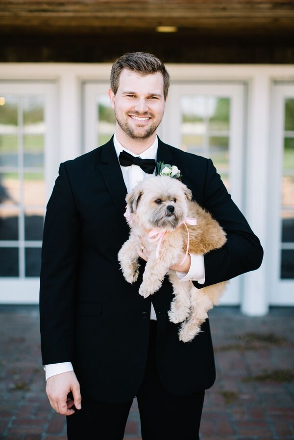 Groom in Classic Black Tuxedo with Puppy