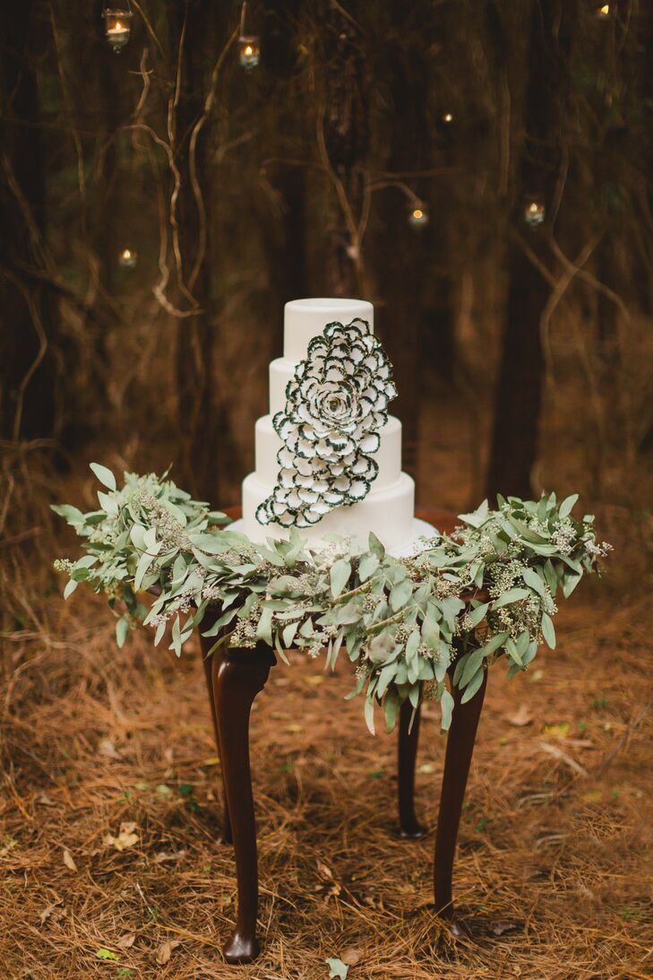 A white fondant four-tier cake made by Ambrosia Cake Creations was decorated with a custom-made flower, with each petal's edges painted black and gold.