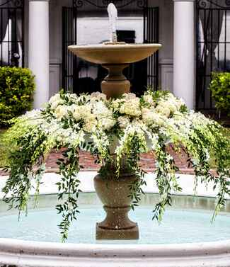Fountain filled with white hydrangea and greenery