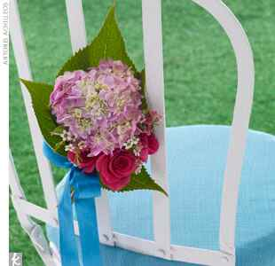 hydrangeas tied to the back of a ceremony chair with a blue cushion
