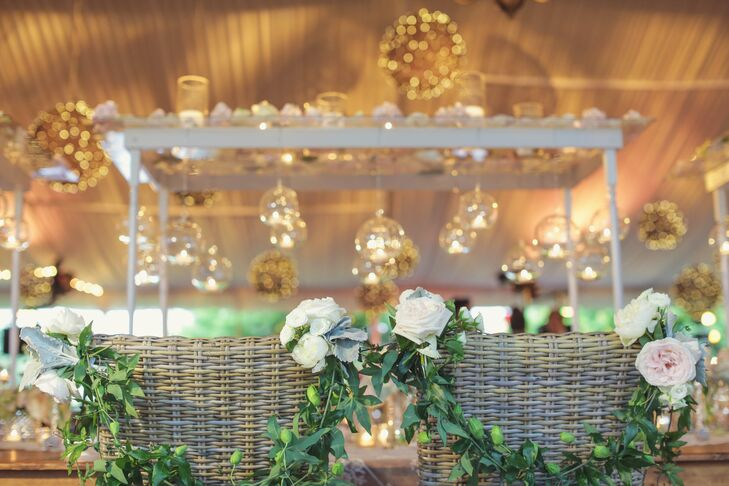 Kellye and Eddie's reception seats were decorated with strands of greenery and ivory and blush roses.