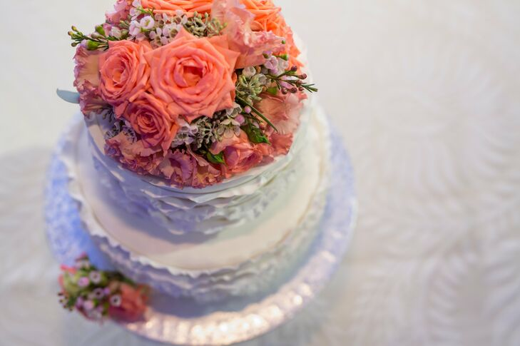 Coral roses decorated the top of the two tier white buttercream wedding cake.