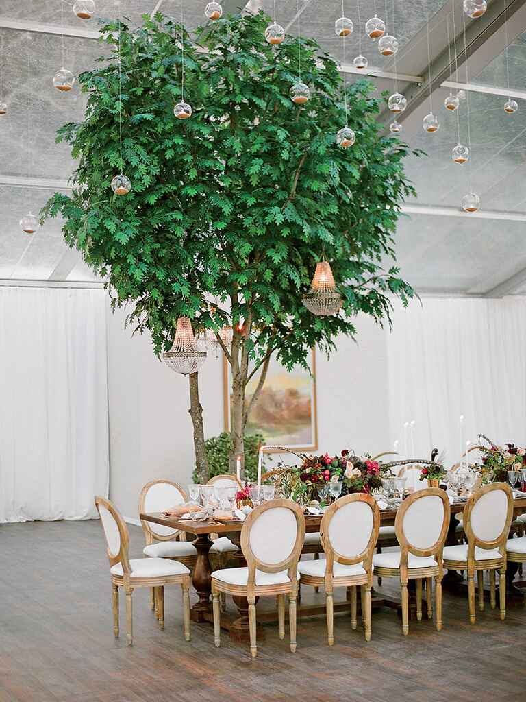 Outdoor tented wedding reception with trees and hanging candles