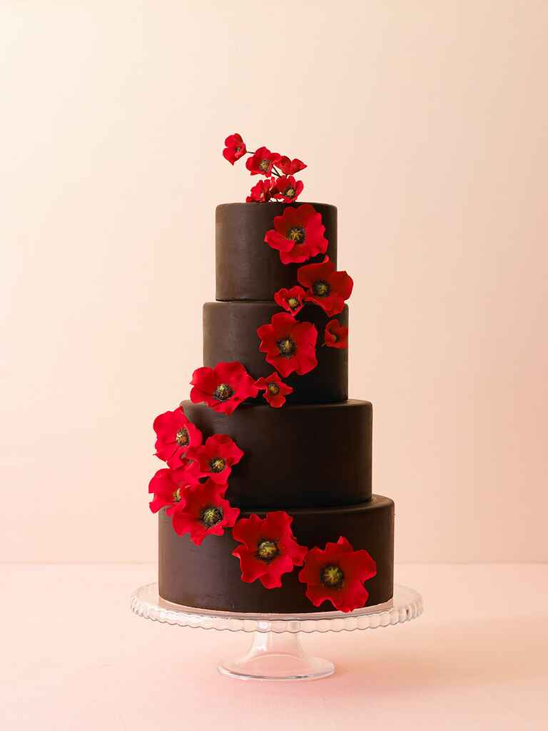 Tall, four-tier chocolate wedding cake with cascading red flowers