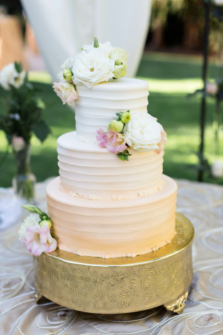 "The couple served a three-tier ivory wedding cake decorated with pastel-colored flowers and displayed on a gold stand. ""We adore a plethora of desserts, so it was hard to decide on just one,"" the couple says. ""They served a triple-tier, pink ombre-swirled cake with three flavors: raspberry cheesecake, pumpkin, and mocha fudge."""