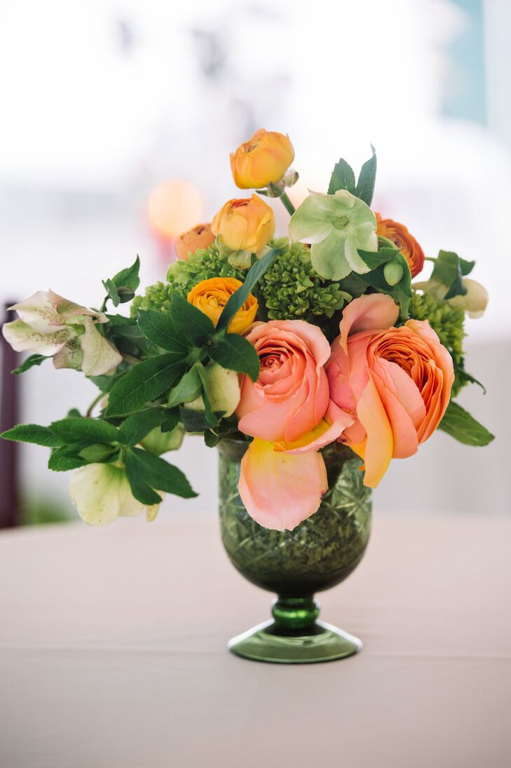 Caroline and Christopher's centerpieces brought in St. Augustine Green's natural atmosphere with lush, natural arrangements. Events by Nouveau arranged each with greenery, green mini hydrangeas, peach roses, mustard yellow ranunculus and orange ranunculus inside a tall green pedestal vase.