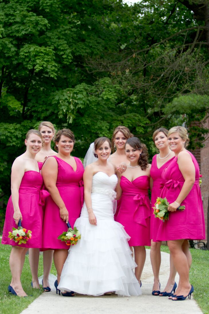 "Nicole's bridesmaids wore short, mismatched Jenny Yoo dresses in the same bright shade of ""Persian Pink."" Every dress featured a stylish sash that they could tie into a bow on the side."